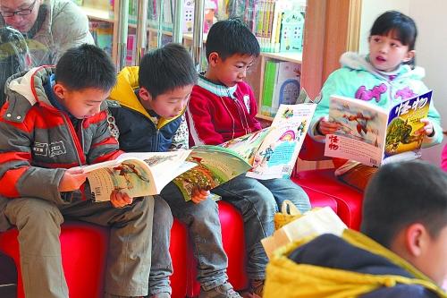 """当记者进入馆内的时候,发现图书馆一层在举办""""剪窗花""""活动,孩子们坐在"""