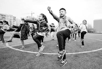 3月22日,鹤壁市湘江小学三年级学生在课间操学习通背拳.