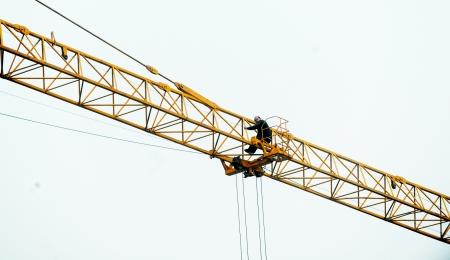 他站在塔吊臂的南侧,身体向北倾斜着