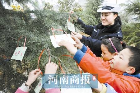 """小学生和警花一起制作了""""心愿卡"""",挂在雪松上."""