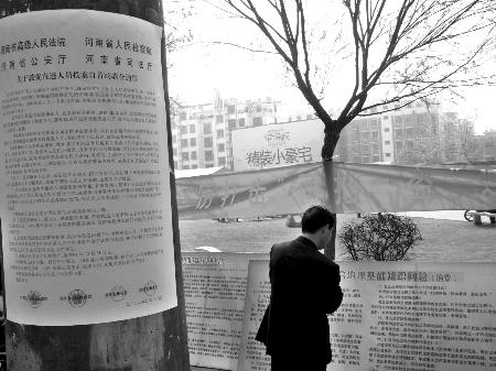 群众认真阅读平安建设宣传展板